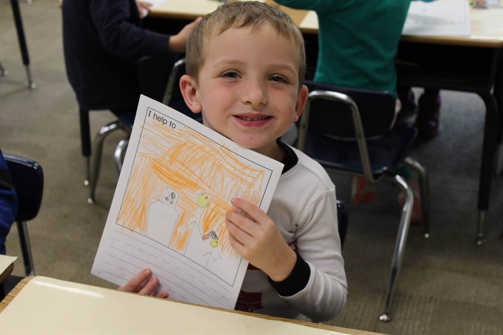 Kindergarten students draw pictures of how they help out at home