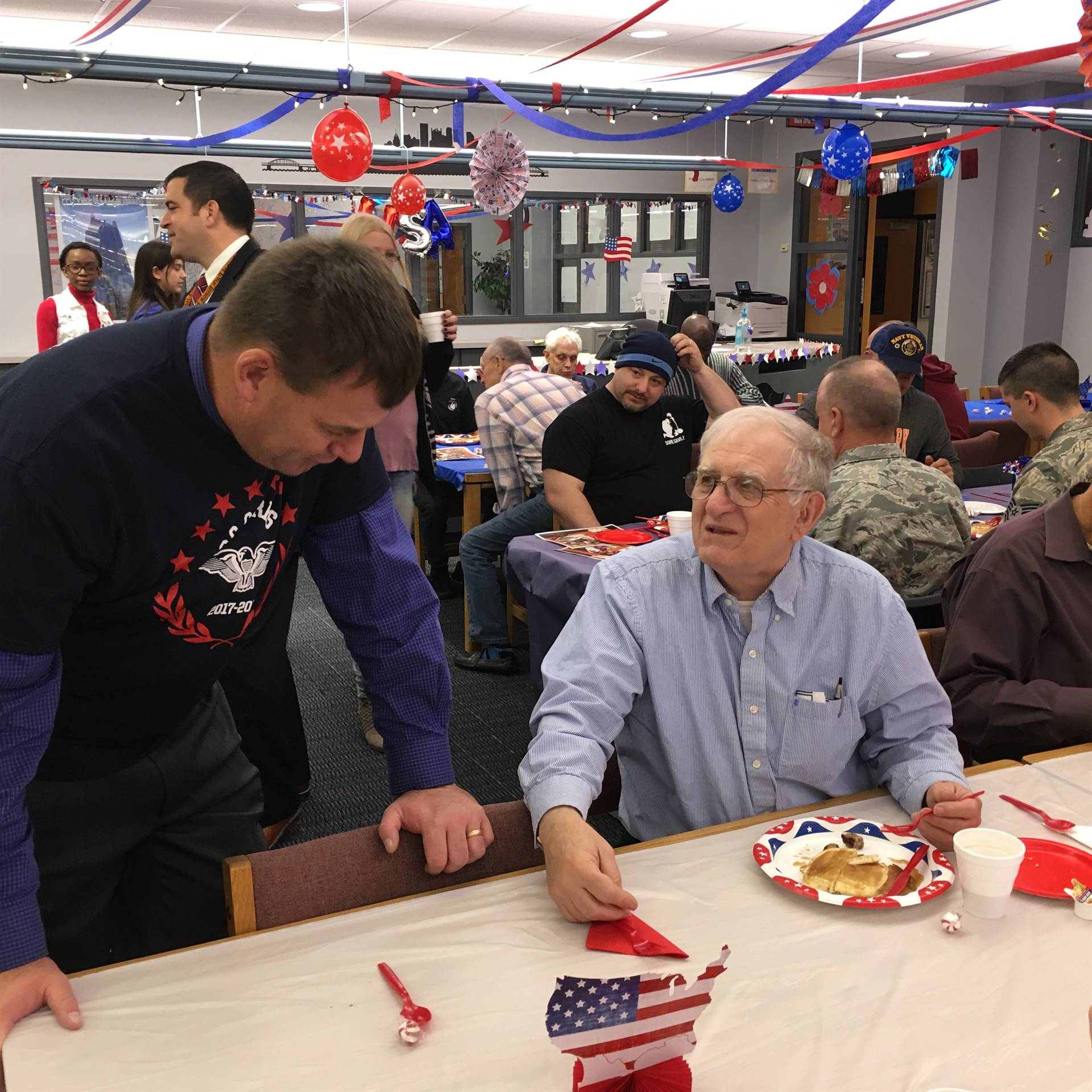 Principal David Muench speaks with a Veteran