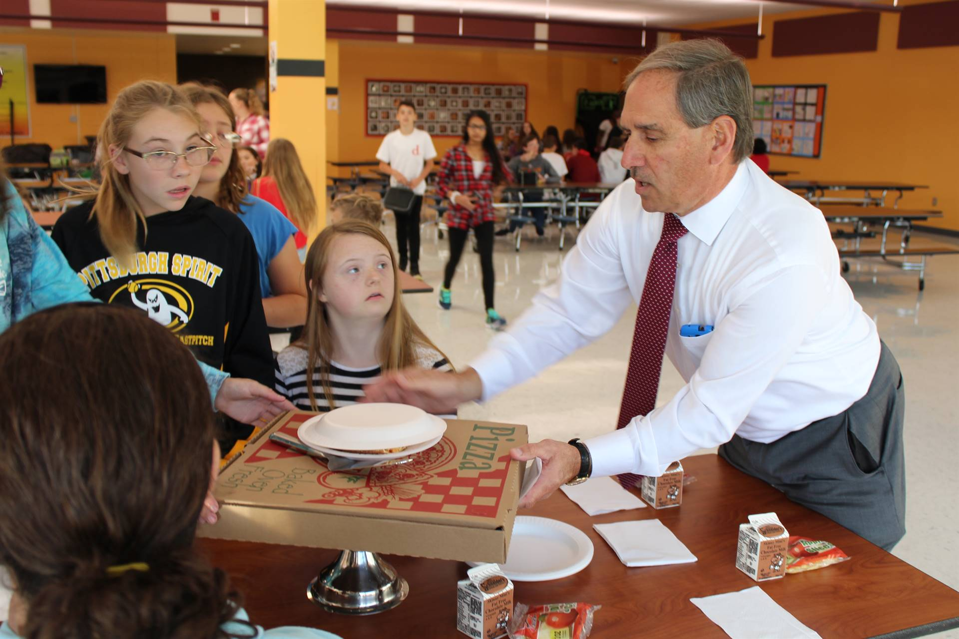Food Service Director Joe Consolmagno delivers a pizza to the table