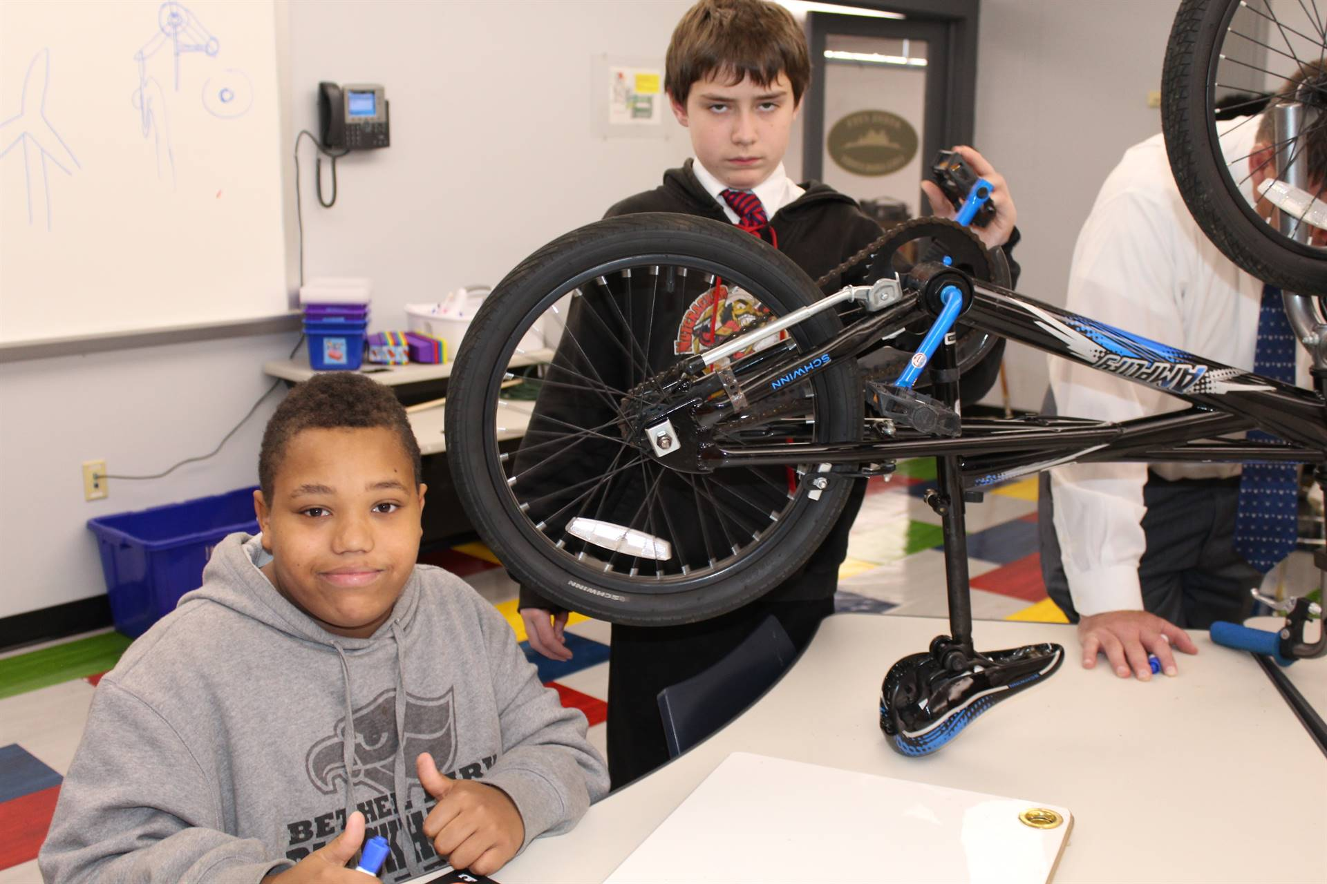 Students look at the bicycle to see how they could use it for the wind turbine