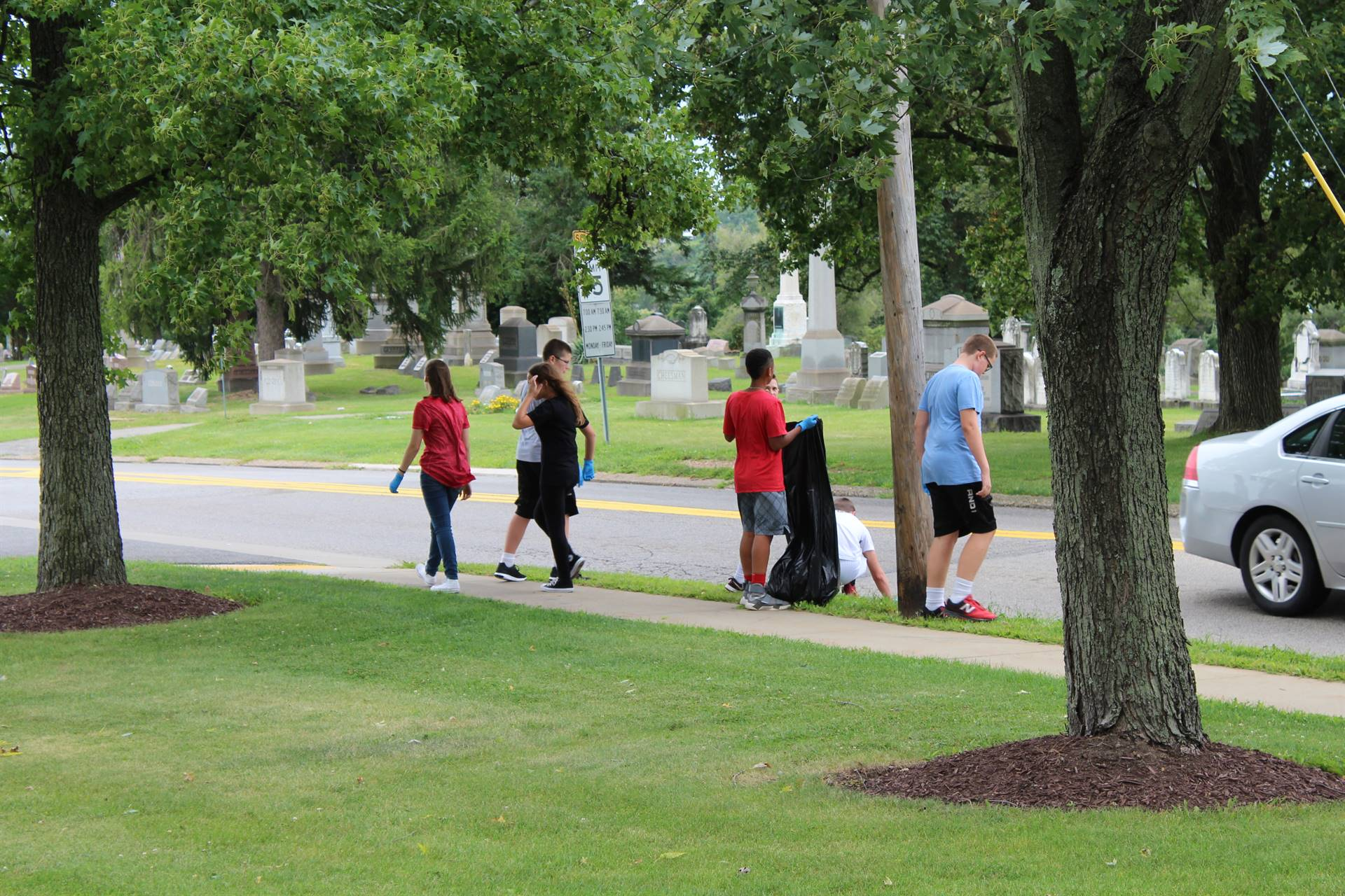 IMS students pick up litter along the curb outside the Administration Building