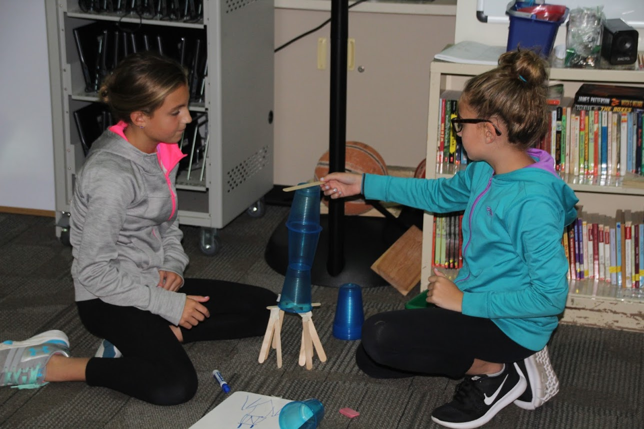 Students add popsicle sticks to strengthen their towers