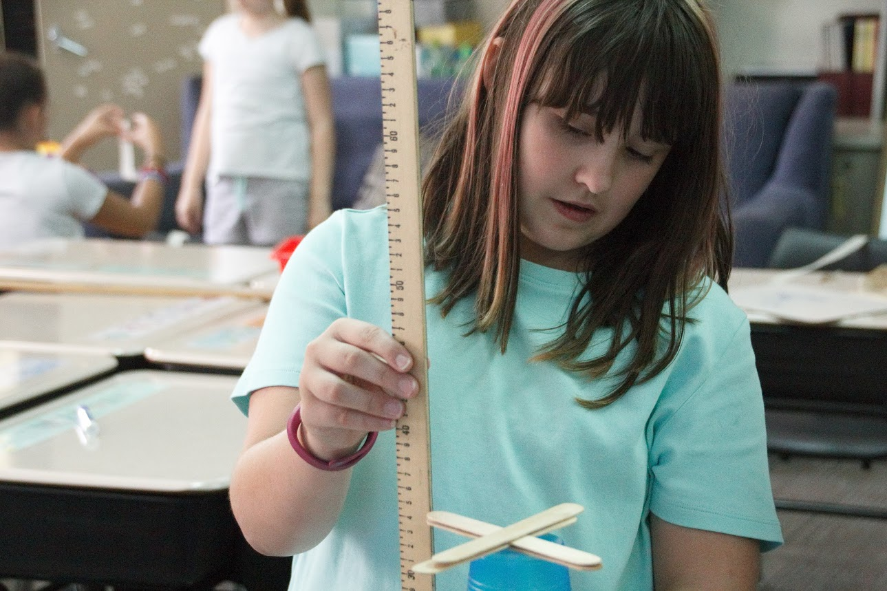 Students measure the height of their towers