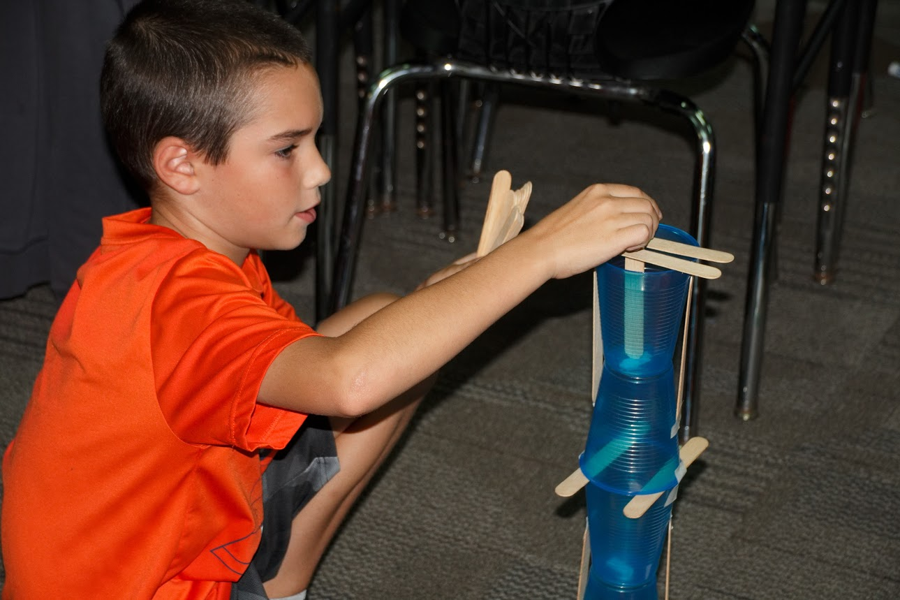 Students add popsicle sticks to strengthen their tower