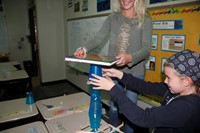 Students try to balance a text book on top of their tower