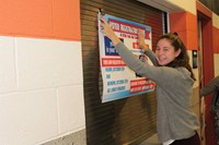 Student hanging a poster with voter registration information on it