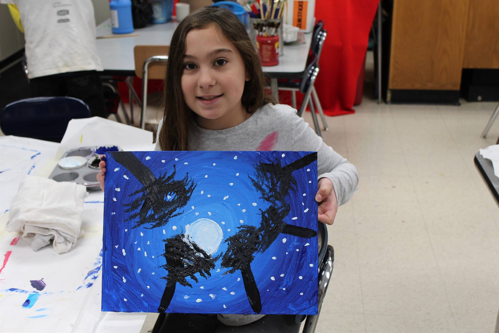 Student holding up painting