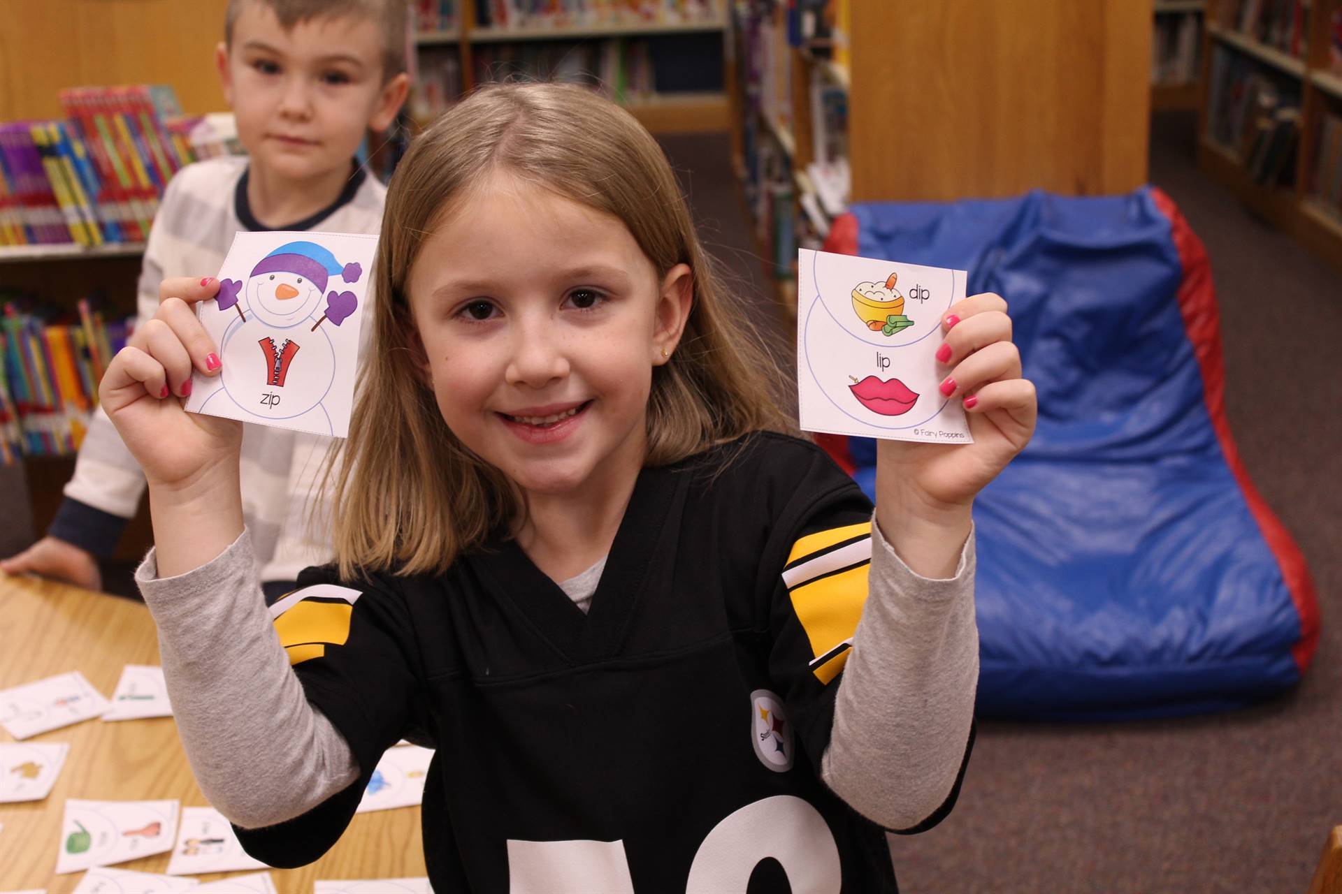 Kindergarten student matching rhyming words using snowman cards