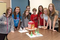 Eight students with their gingerbread house