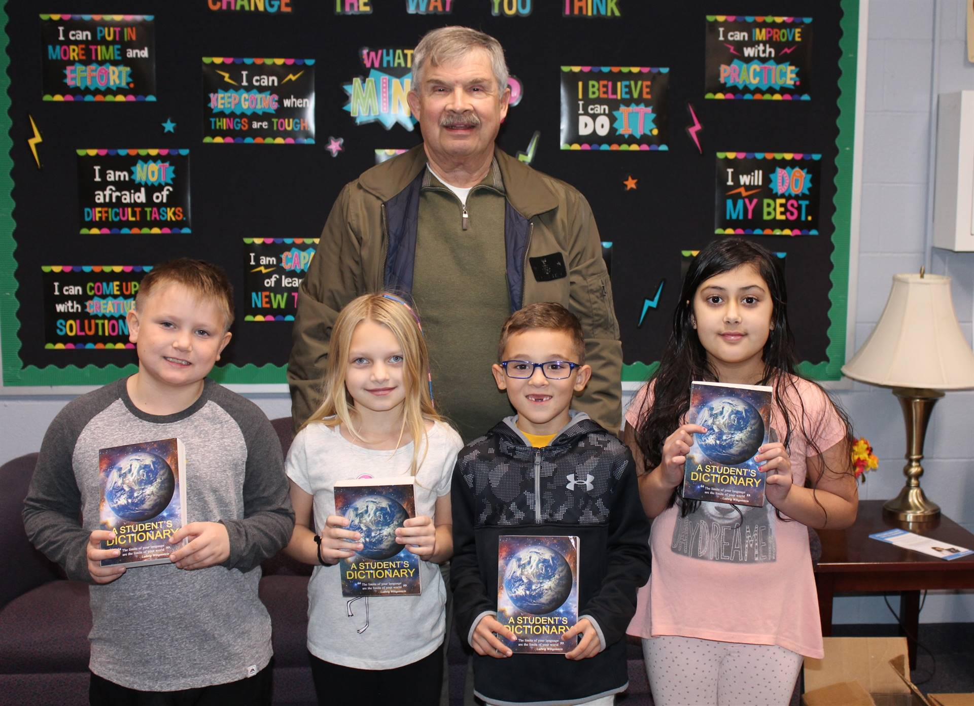 Four fourth grade students with Rotarian Bob Bauer