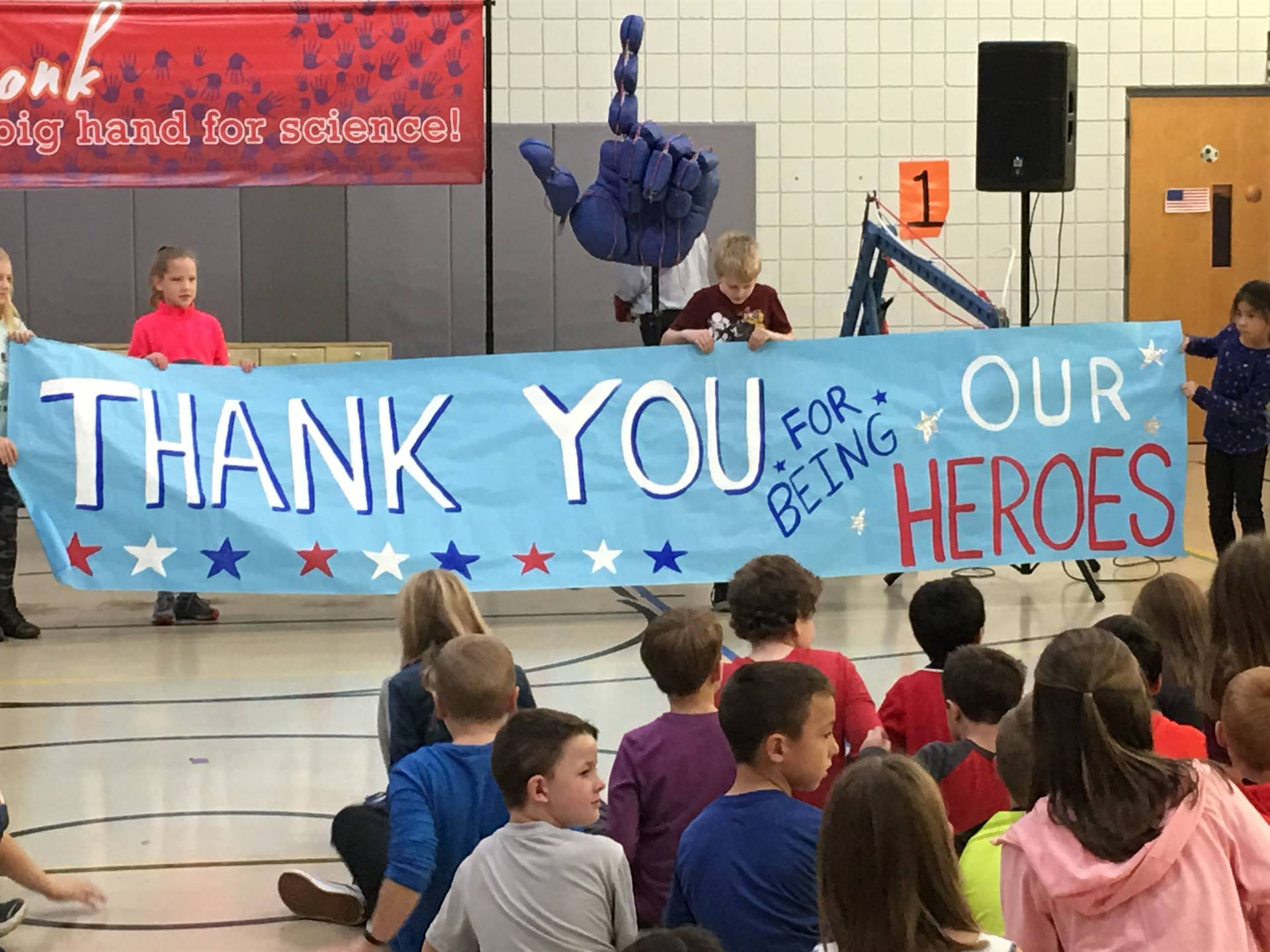 Students holding a Veterans Day Thank You Banner