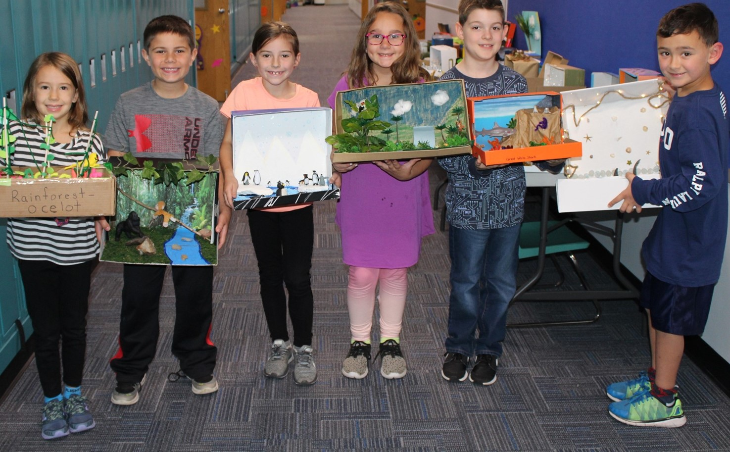 Six students holding their habitat dioramas