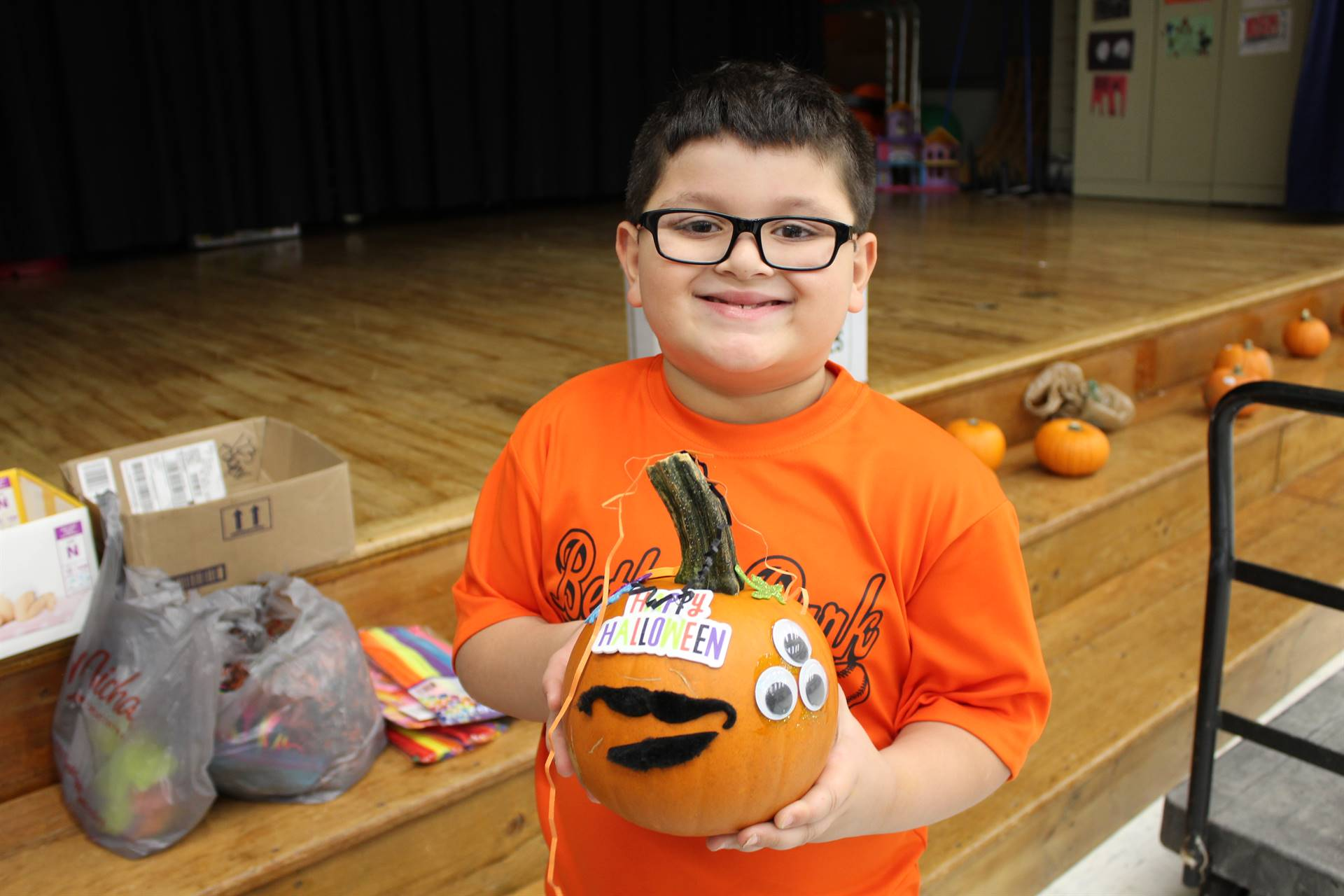 Student holding the pumpkin he decorated at the Fall Festival