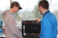 Mr. Winschel shows a student how to program the 3D printer
