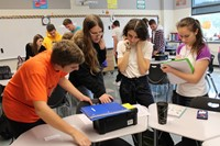 Four students working to open the tool box