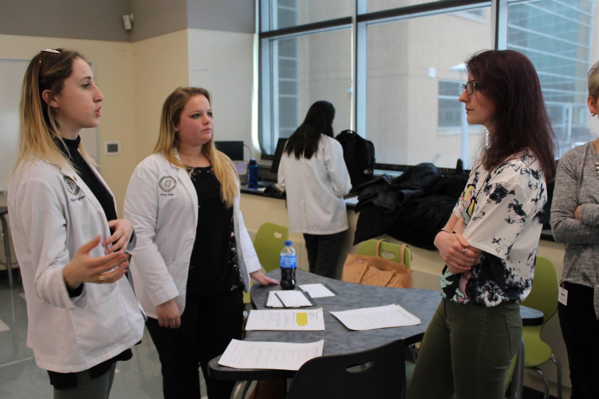 BPHS student talking to two Pitt Pharmacy student
