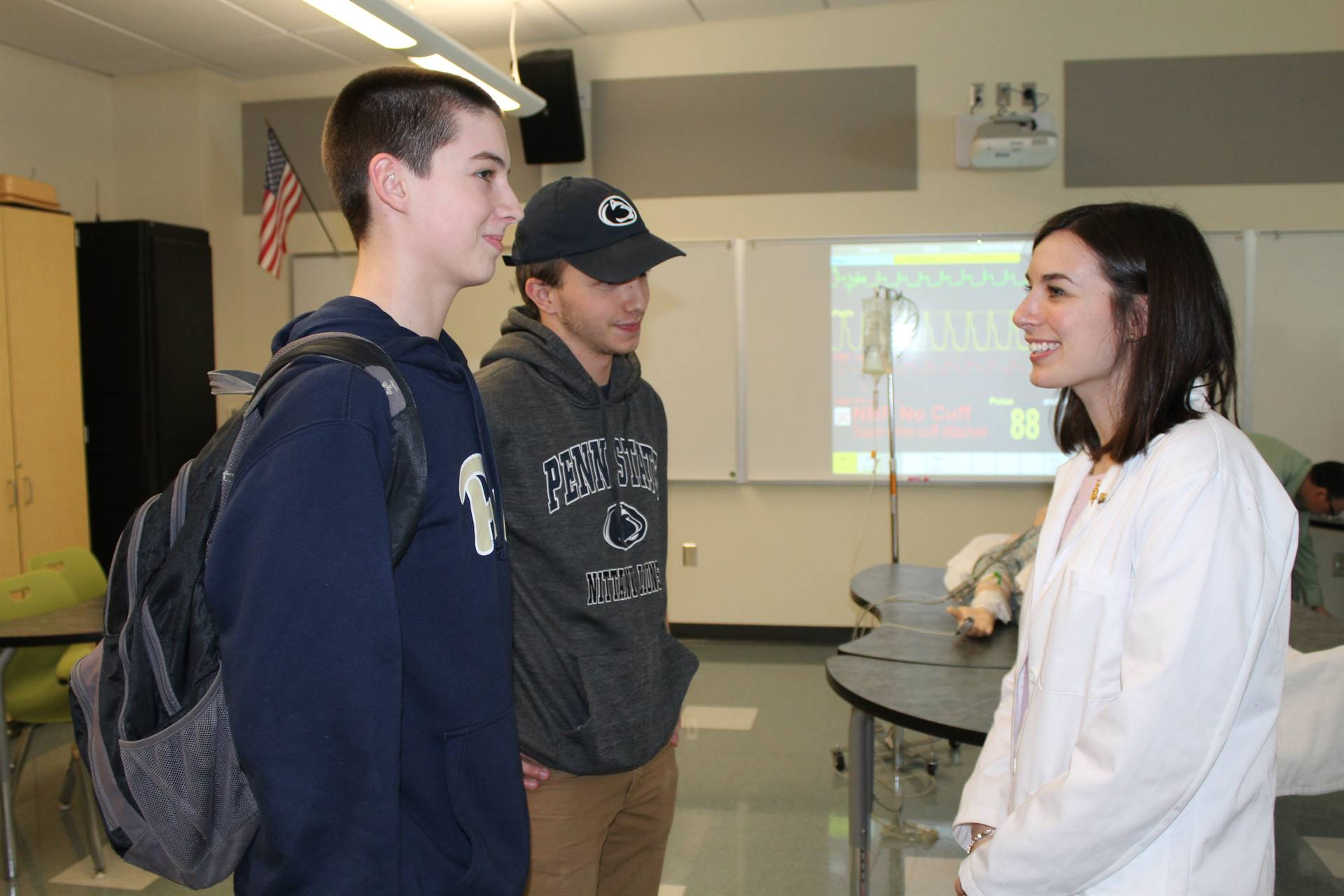 Two BPHS students talking to a Pitt Pharmacy student