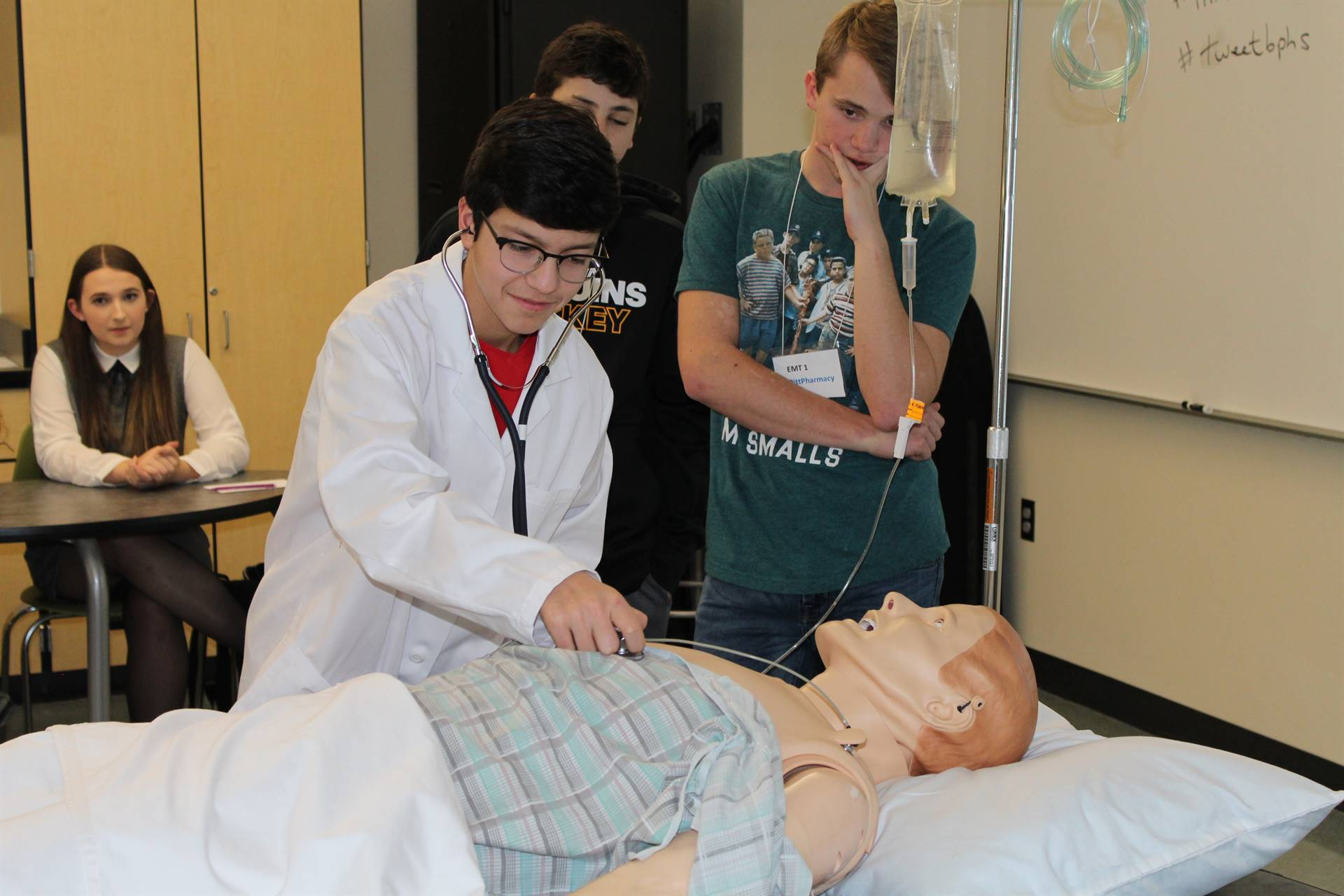 Student listening to the Sim Man's heart with a stethoscope