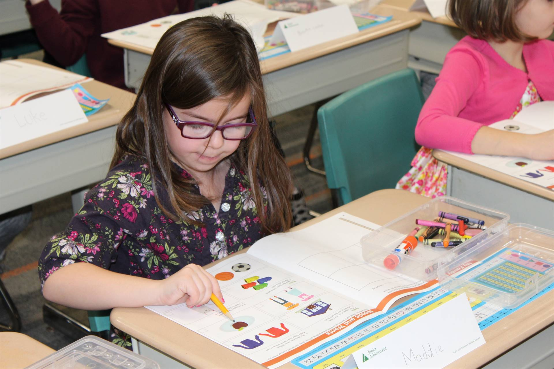 Franklin student pointing to something in her work book