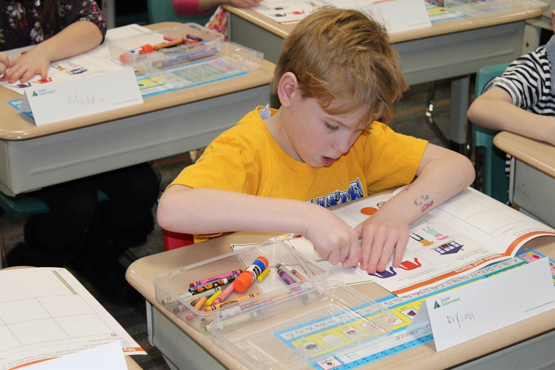 Franklin student putting a sticker in his work book