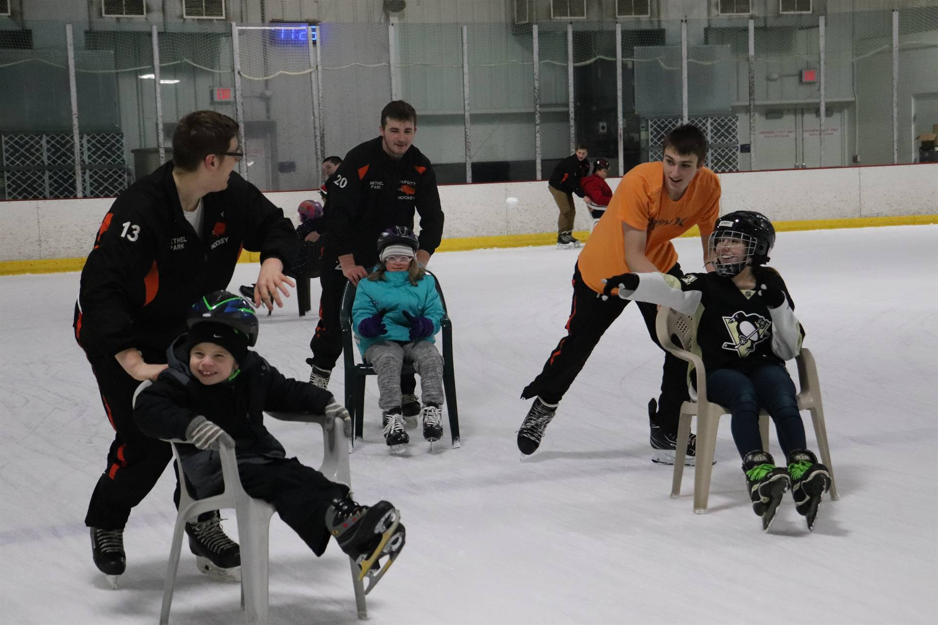 Hockey players pushing students on the ice in chairs