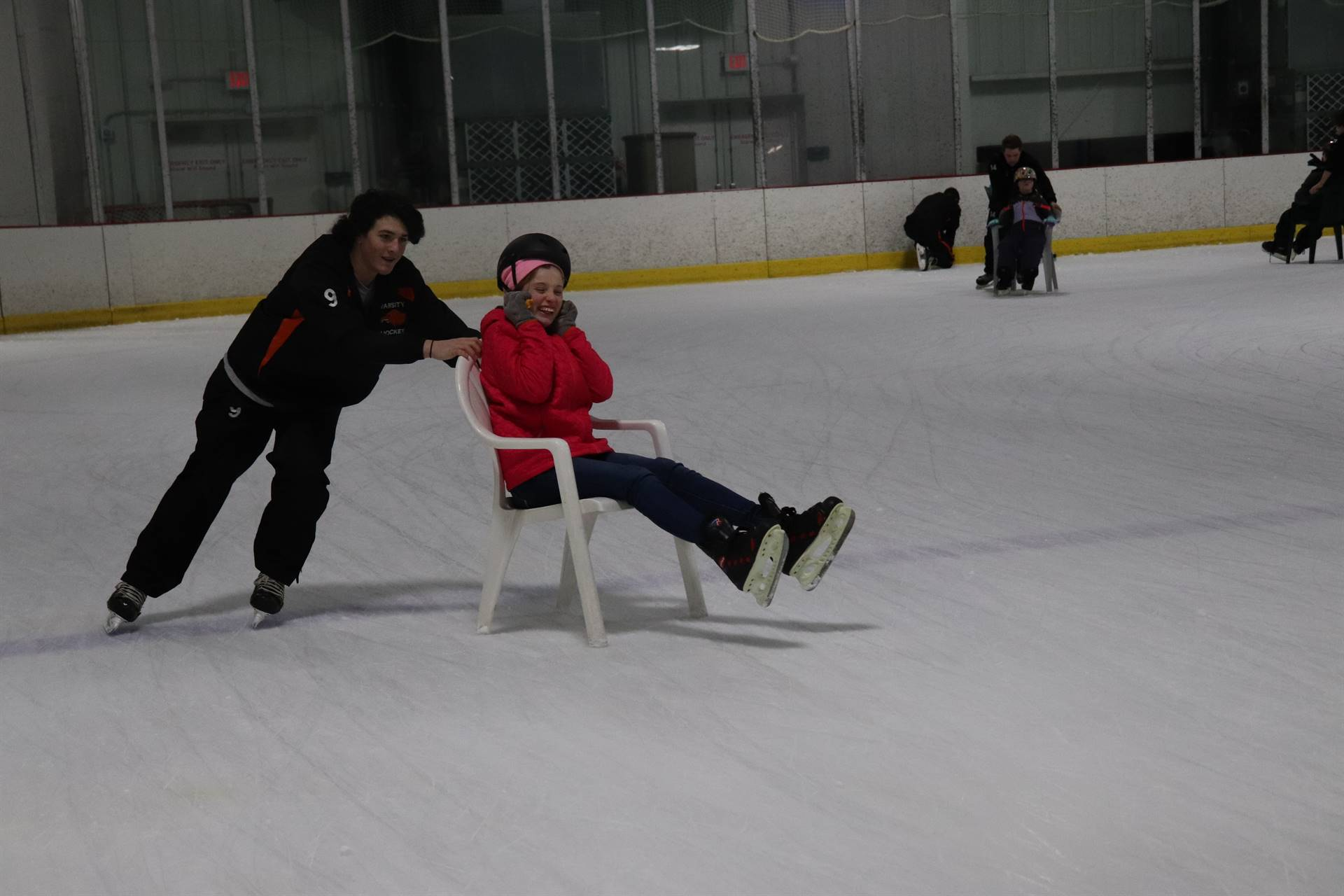 Hockey player pushing a student on the ice in a chair