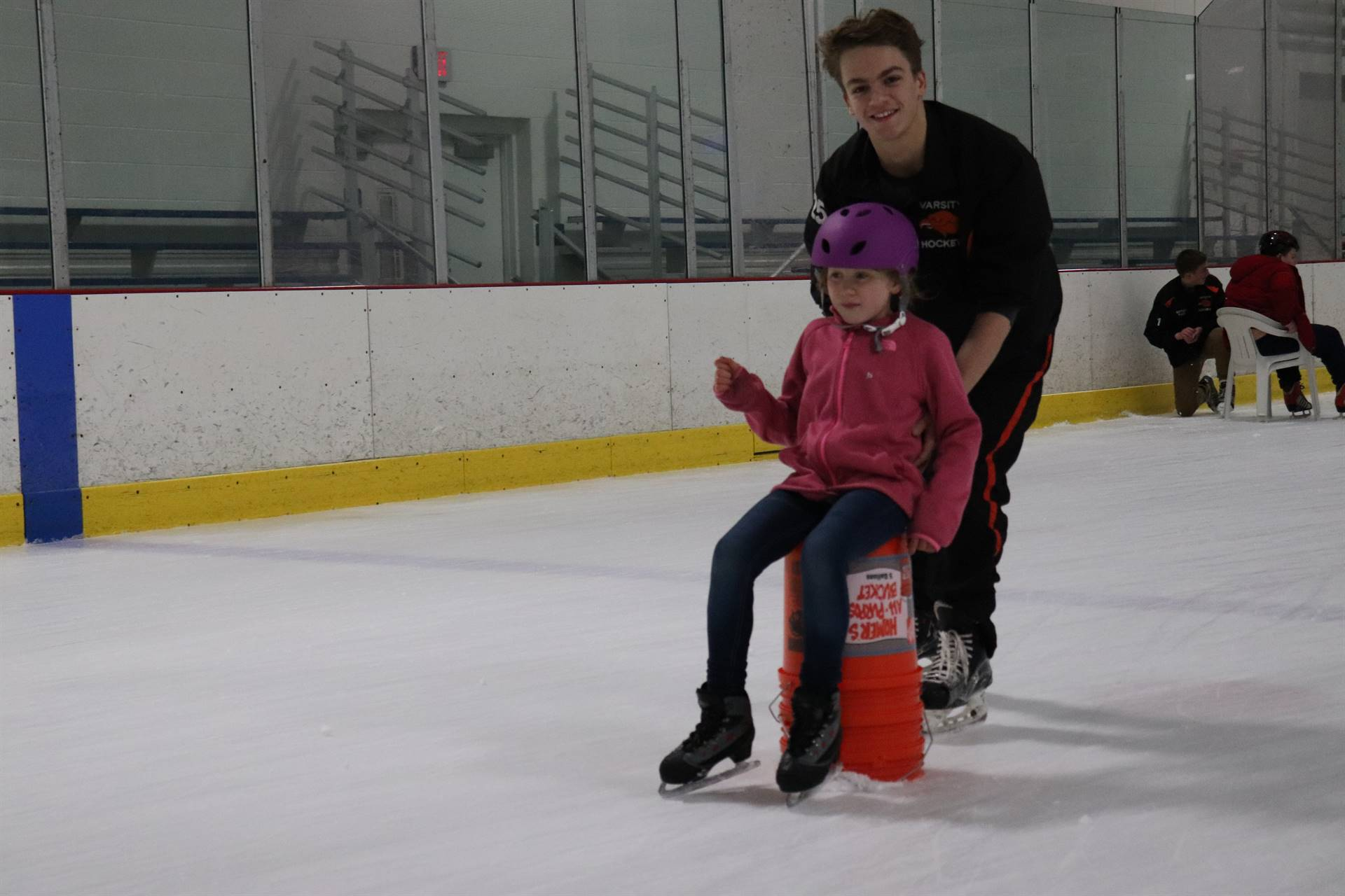 Hockey player pushing a student around the ice on a chair