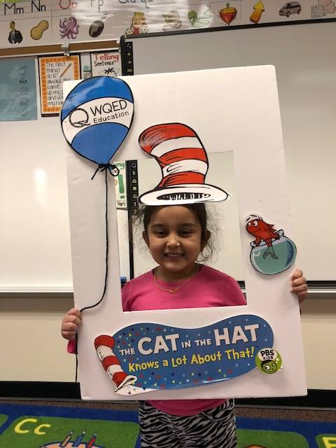 Student holding a Cat in the Hat frame