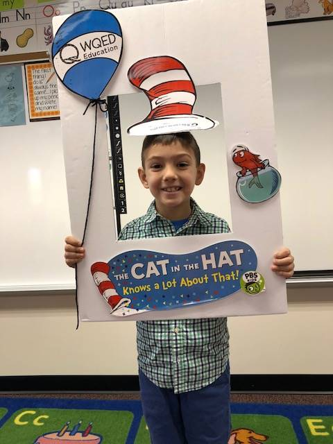 Student holding a Cat in the Hat picture frame