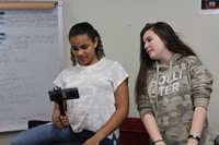 Two students looking at the Google app on a cell phone