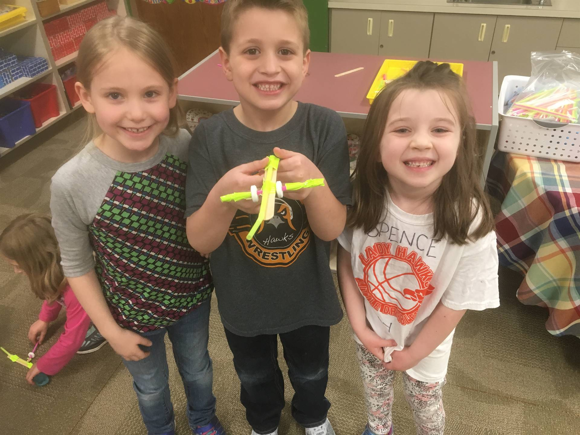 Three kindergarten students holding a balloon wheel car they made