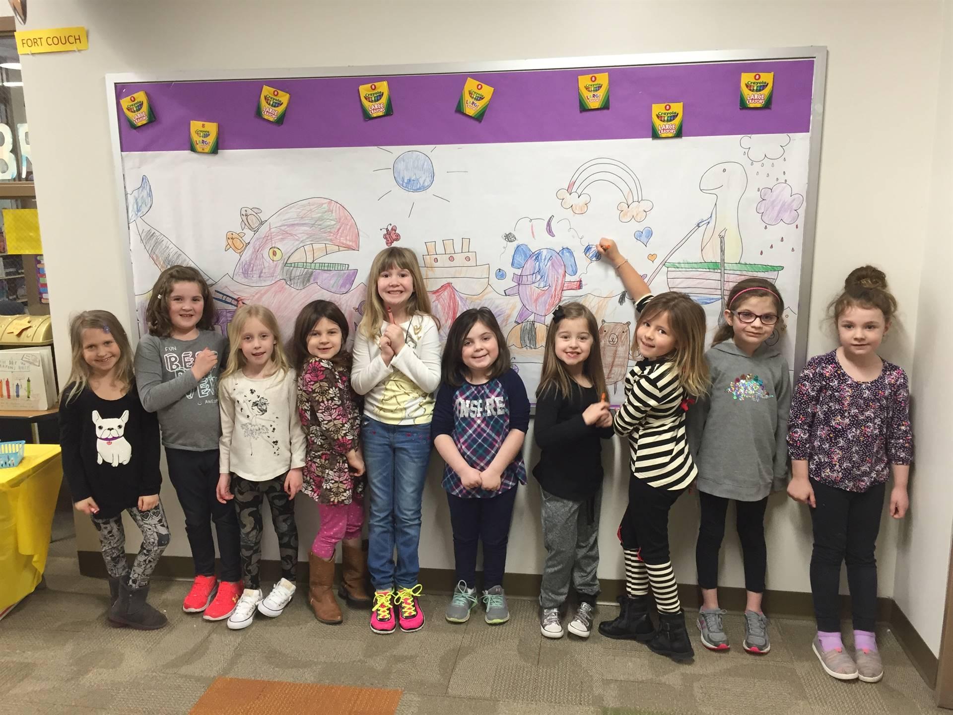 Kindergarten students coloring a bulletin board in the school lobby