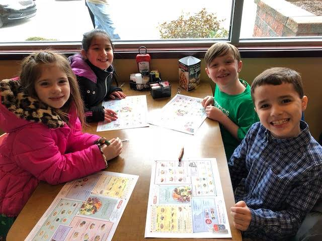 Four students coloring placemats at a table
