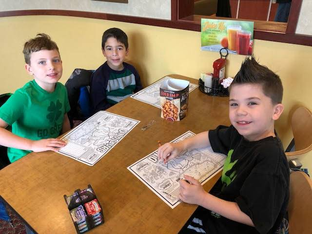 Three students coloring placemats at a table