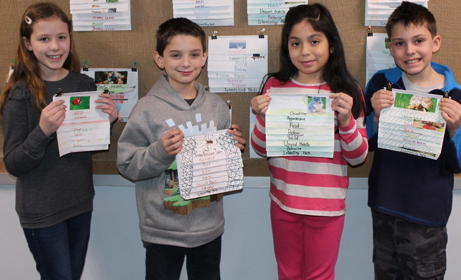 four students holding their animal flip books