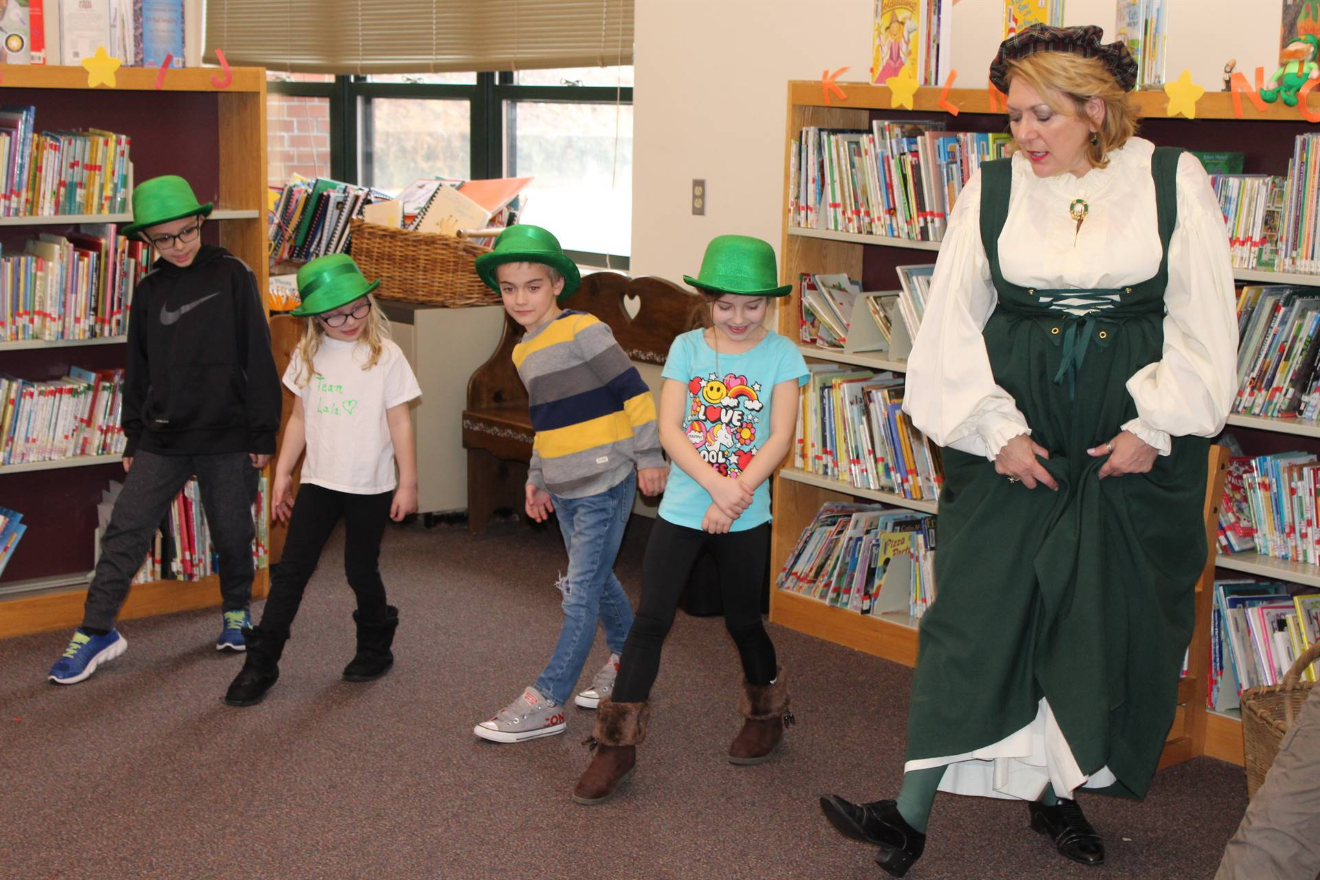 Four students learning an Irish dance from an Irish storyteller