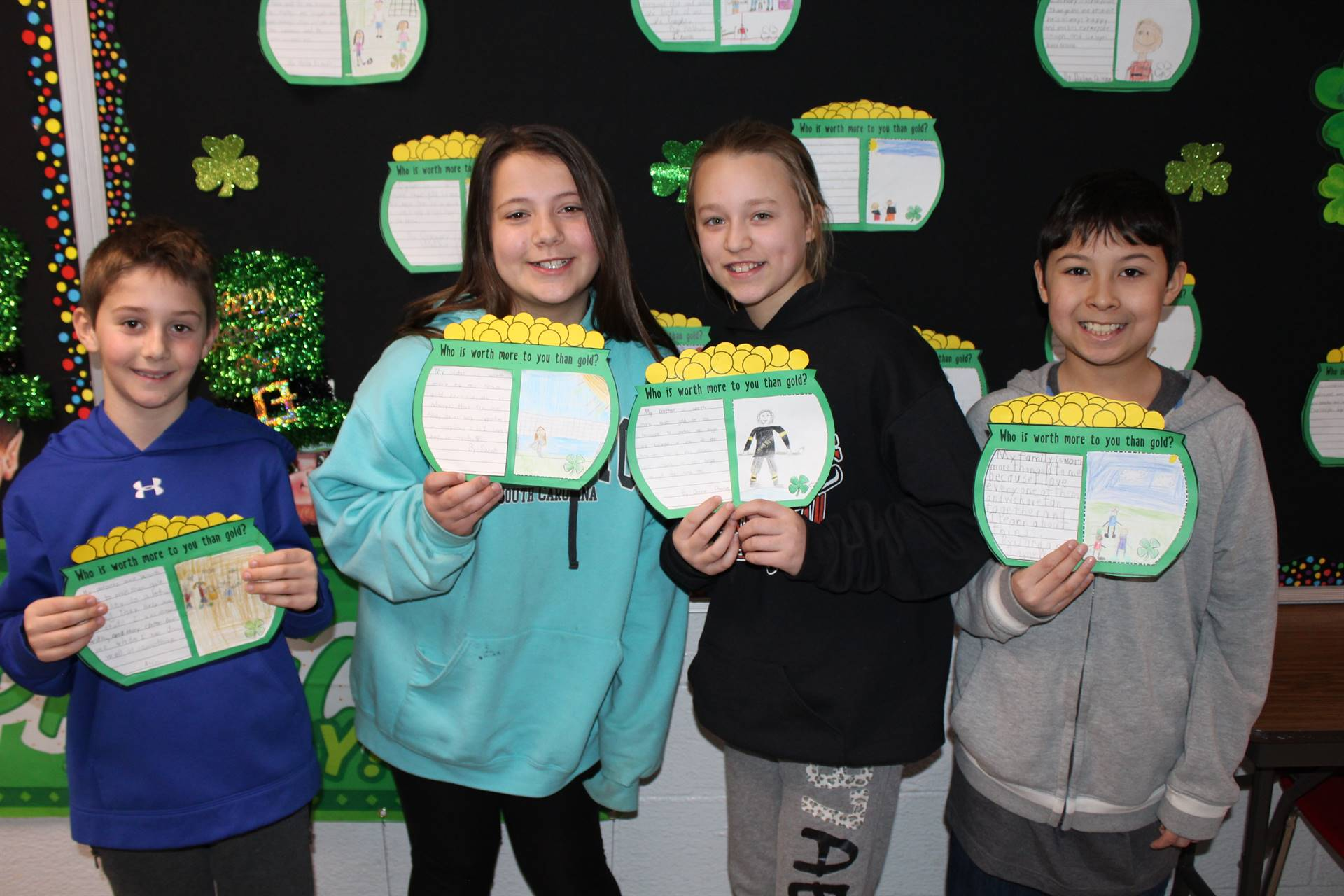 Four students holding paper pots of gold