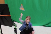 Student moving her puppet in front of the green screen