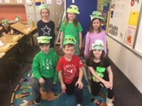 Six students wearing the leprechaun hats they made