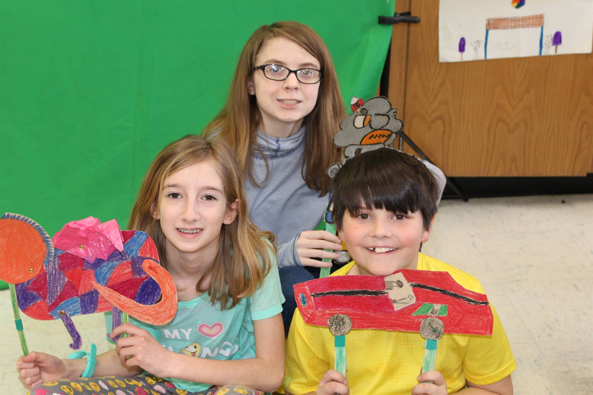 Three students with their puppets in front of a green screen