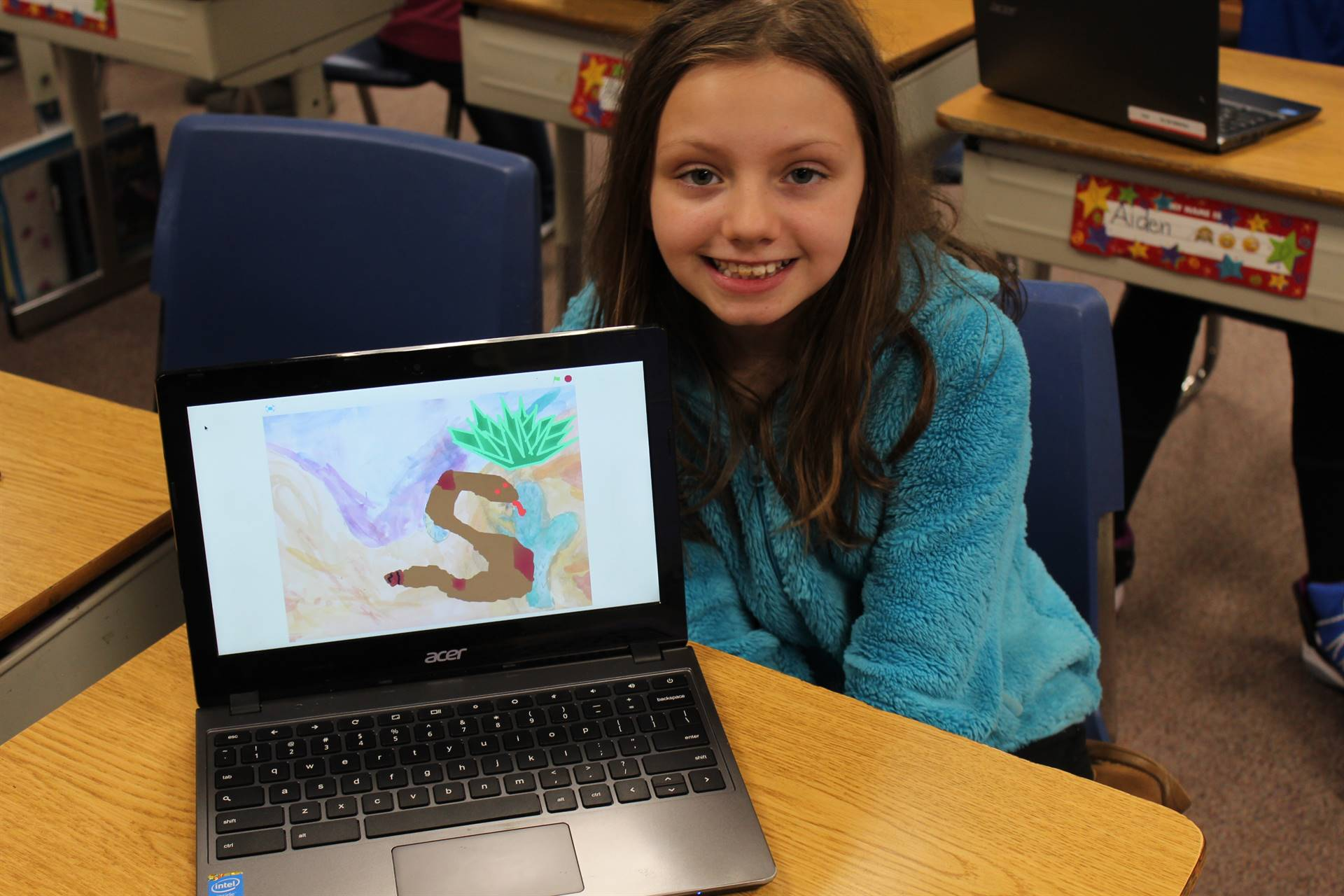 Fourth grader with her Scratch presentation on a computer