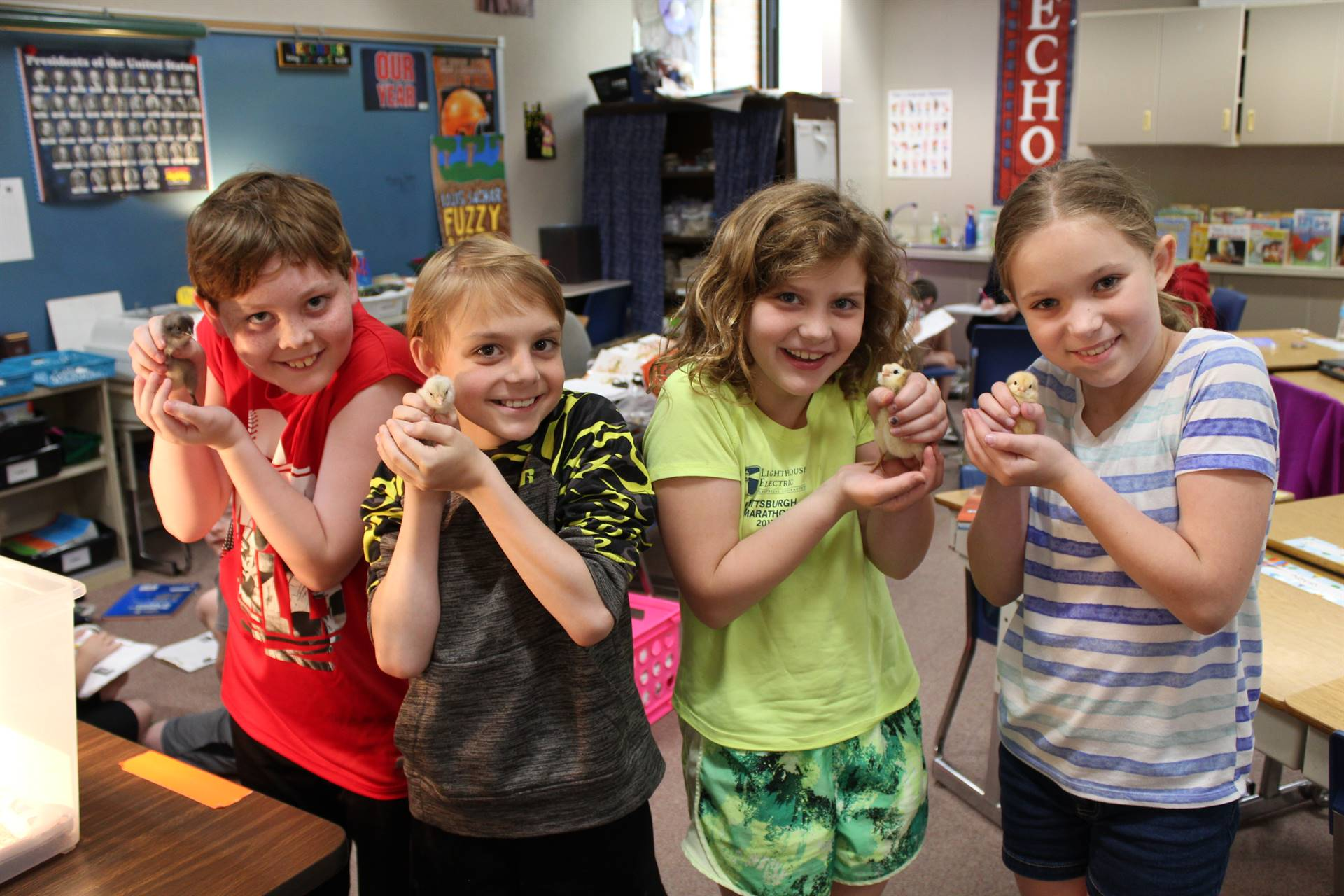 Four Fourth graders holding baby chicks