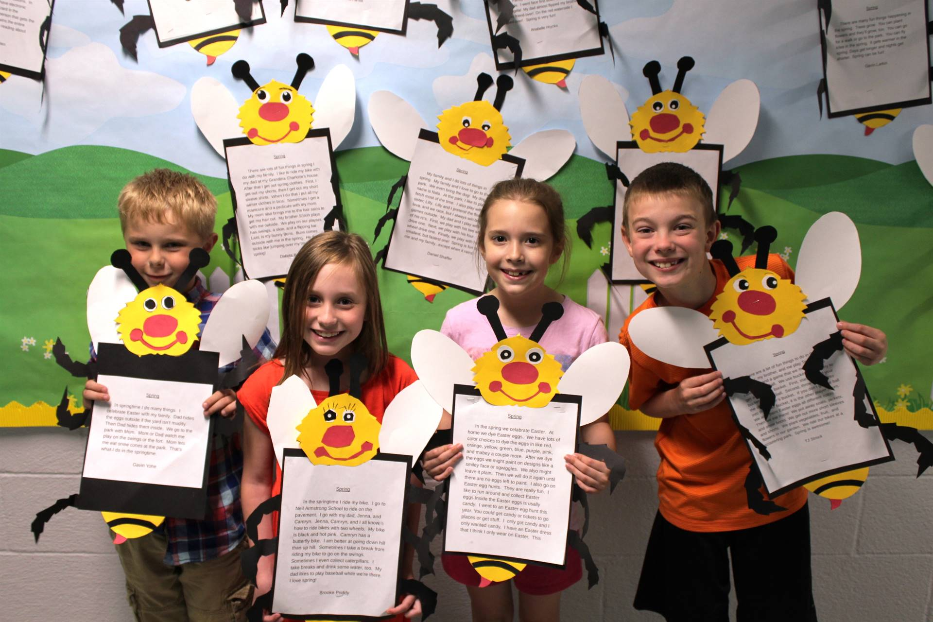 four students holding their spring essays