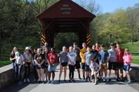 group of students in front of a covered bridge