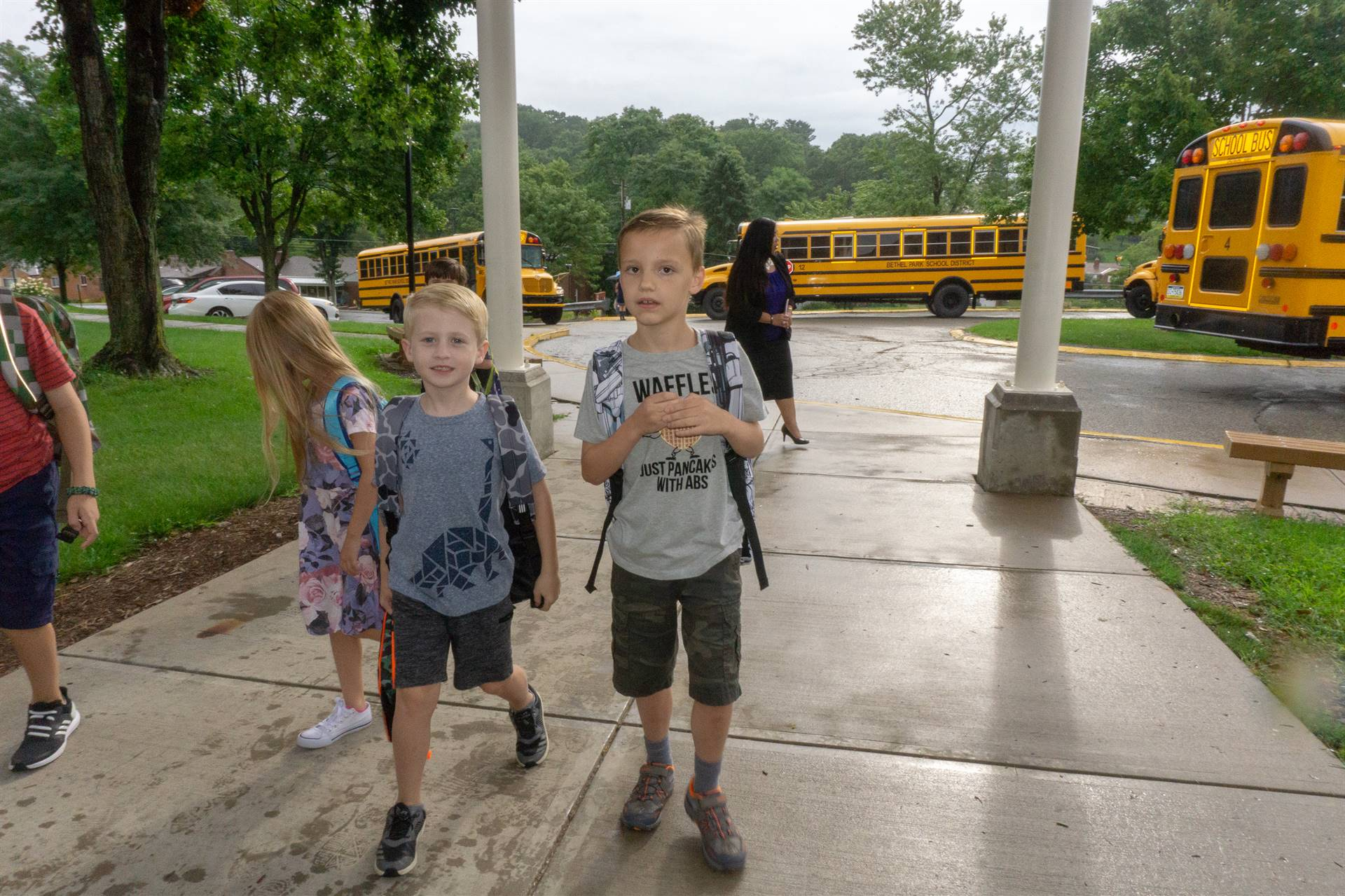 Two boys entering school on the first day.
