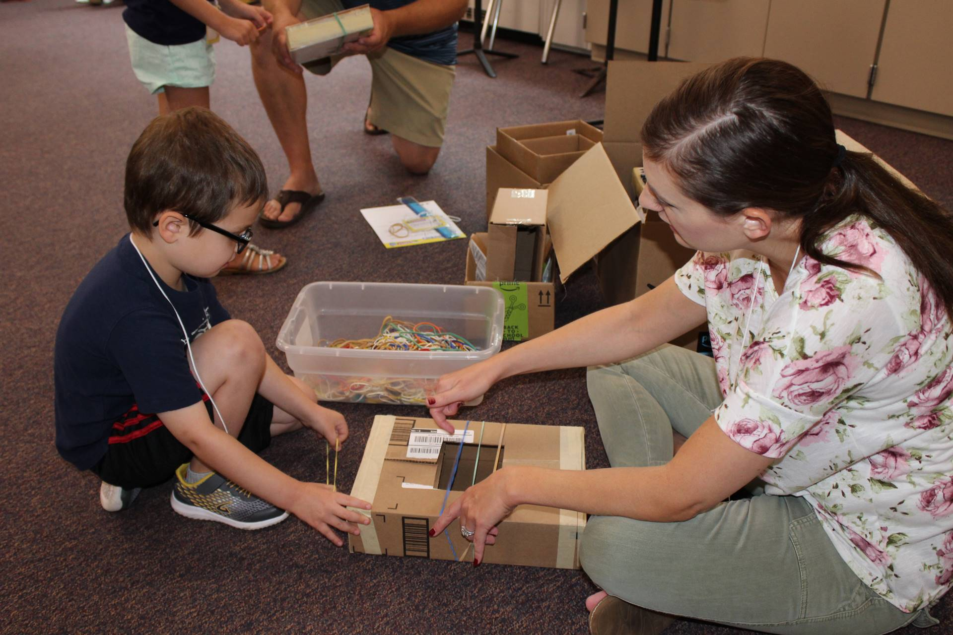 Student and parent making a musical instrument out of a box and rubber bands