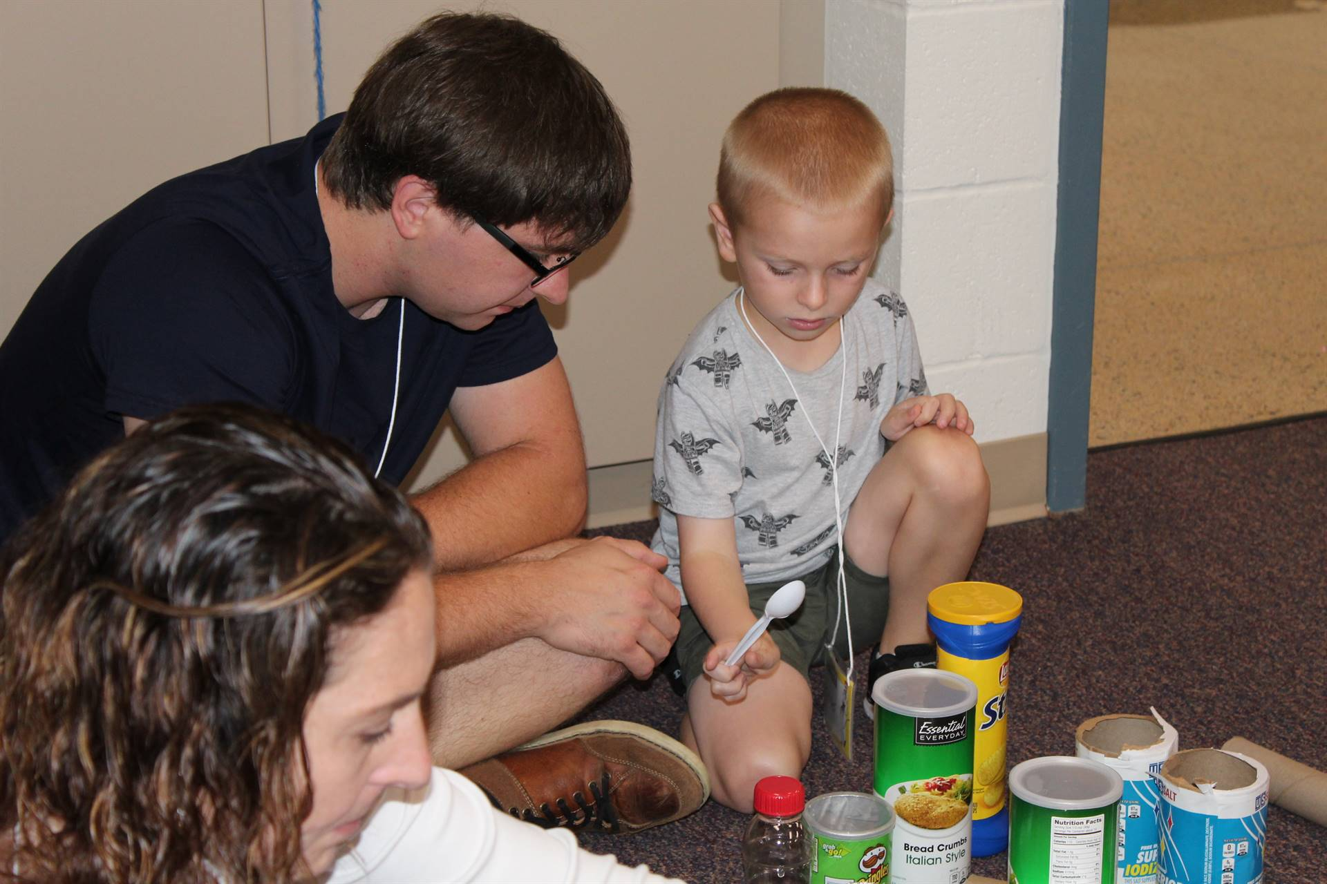 Parent and student using a spoon to beat on potato chip canisters to make sounds