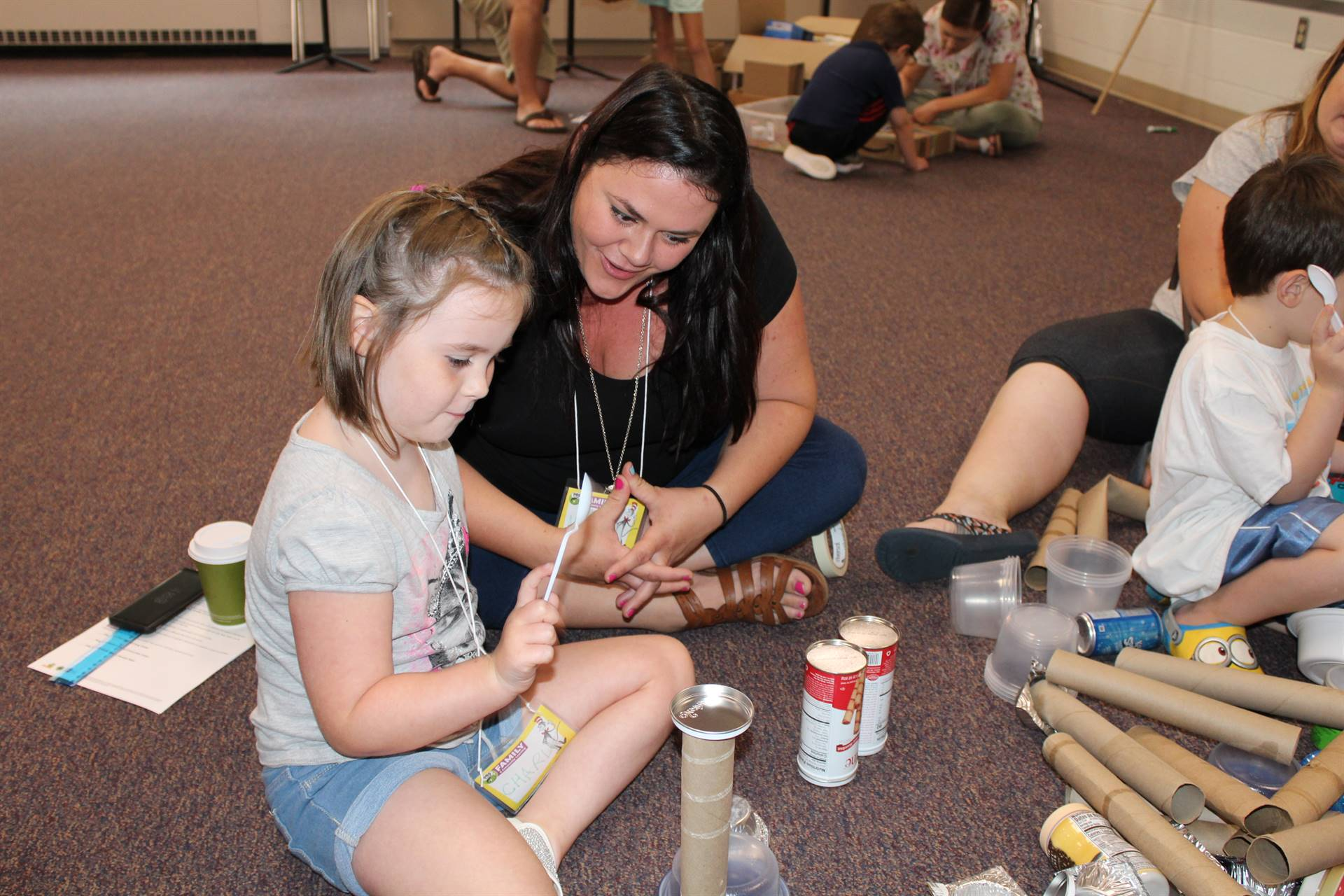 Student and parent using a spoon to make sounds by beating on an empty paper towel roll