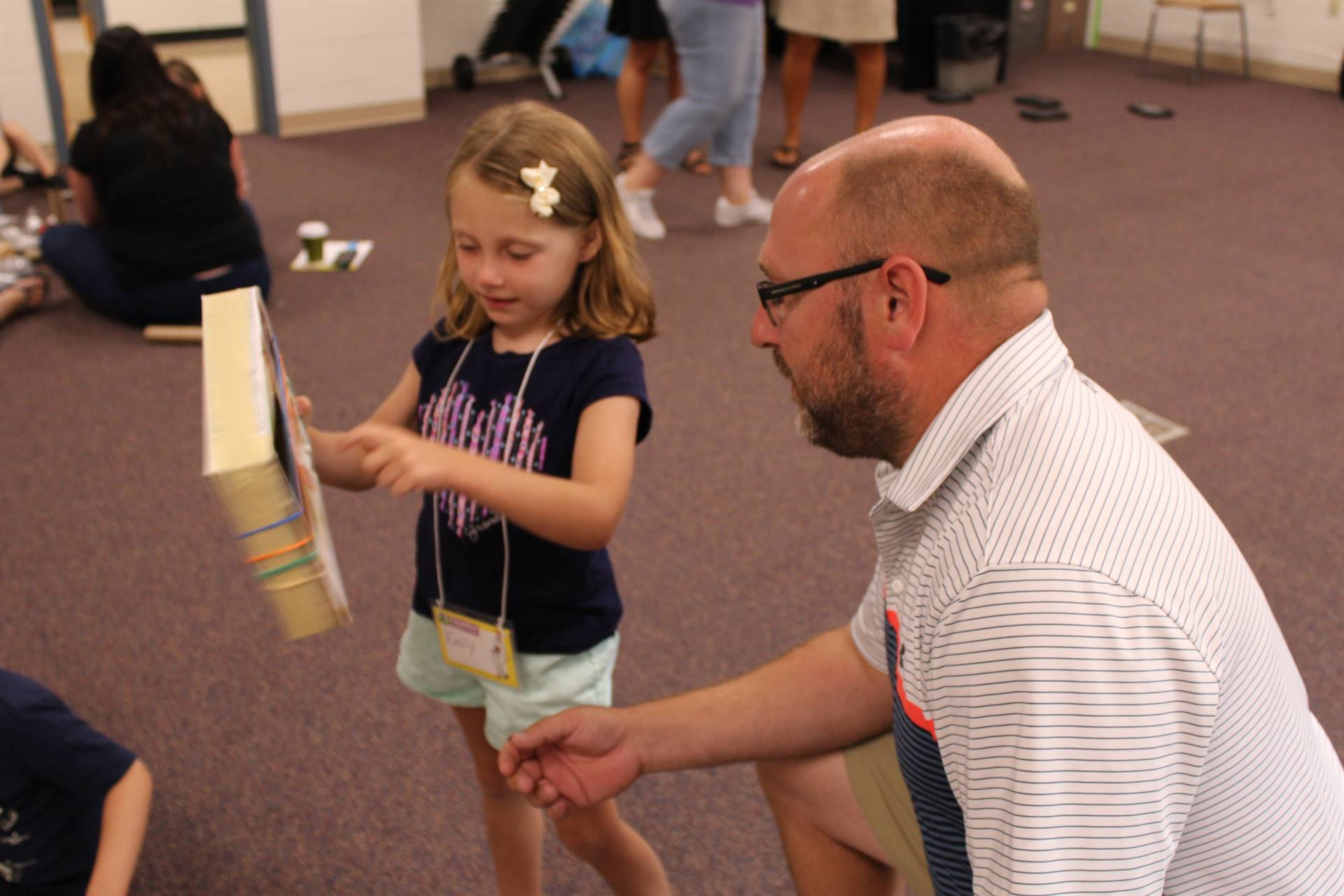 Student showing parent how to strum on an instrument made from a box and rubber bands