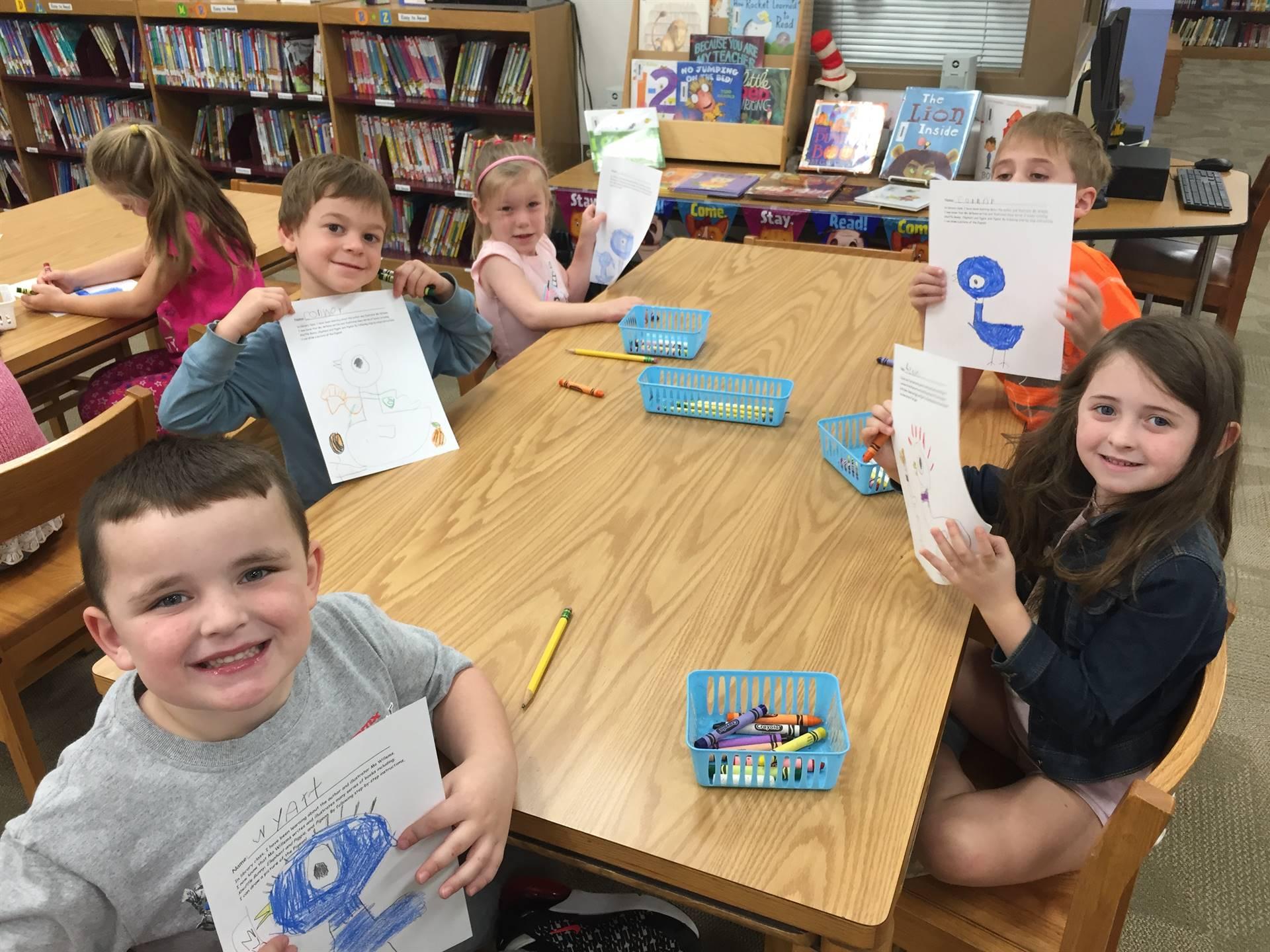 Five Kindergarten students holding up their work